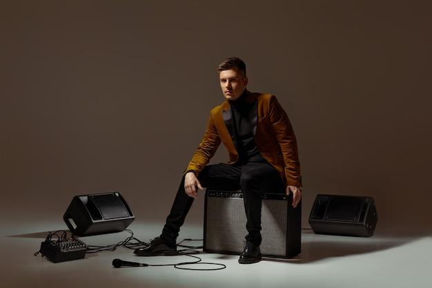 Handsone singer in suit sitting on a musical column