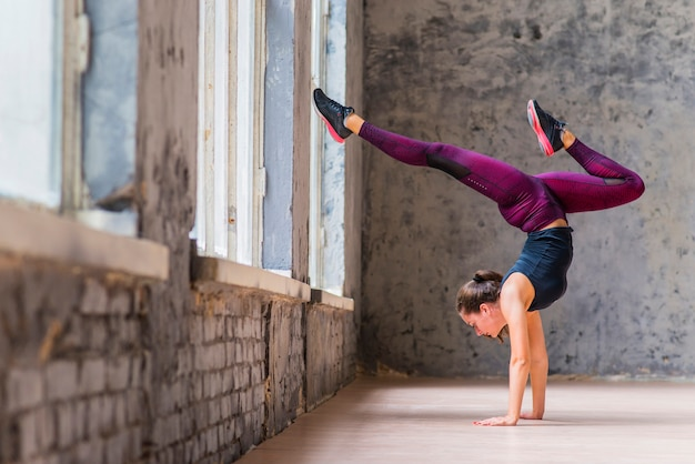 Handstand йоги женщина, занимающаяся йогой вниз по дереву