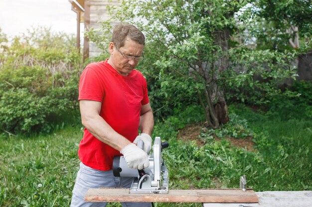 Ручная работа, строительство домов, инструменты. плотник в перчатках пил циркулярной электропилой. красная футболка, серые брюки, на фоне зеленой травы и деревьев.