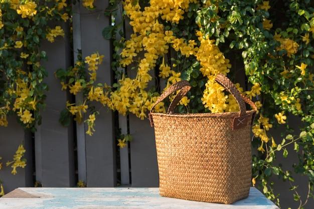 Handwoven beautiful wicker handbag on blue wood table with fresh yellow flowers