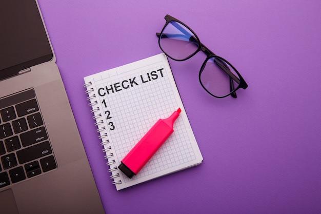 노트북 키보드와 빈 노트북에 필기 검사 목록