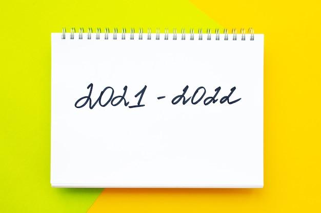 Рукописная надпись в белом блокноте на ярко-желто-зеленом фоне нового учебного года