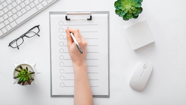 할 일 목록을 메모장에 있는 빈 목록에 필기합니다. 여성의 손은 사무실 직장에서 태블릿에 메모를 합니다. 여성의 손은 흰색 테이블에 있는 업무용 책상에 있는 노트북 종이에 씁니다. 상위 뷰 긴 웹 배너