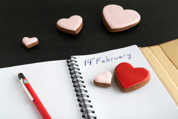 ノートとハート型のクッキーの手書きの碑文2月14日。バレンタイン・デー。
