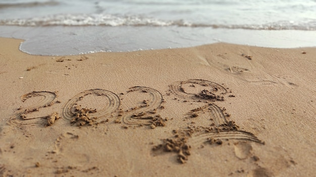 Handwritten inscription 2020 and 2021 on sand of sea beach. background