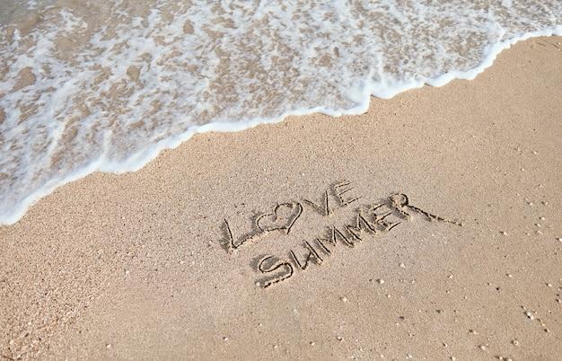 손으로 쓴 비문, 편지, 나는 물로 씻겨 나가는 파도 표면의 젖은 모래에 여름을 사랑합니다. 여름 컨셉