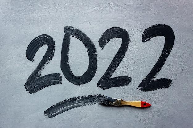 灰色の背景に黒インクで手書きのレタリング2022。近くにペンキの入ったブラシがあります。新年とクリスマスのコンセプト。