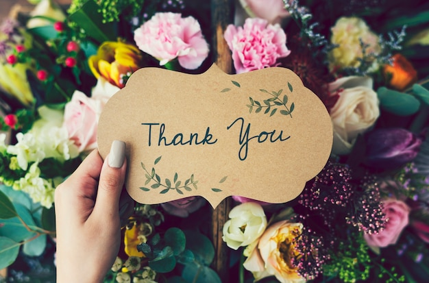 Handwritten thank you card with floral background