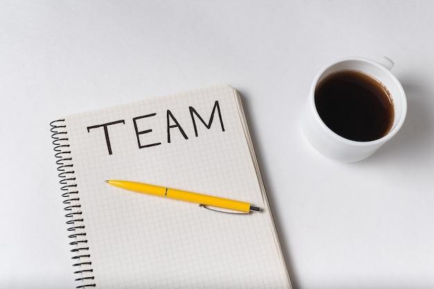 Рукописное слово команда. надпись в блокноте. кружка с кофе на белом фоне.