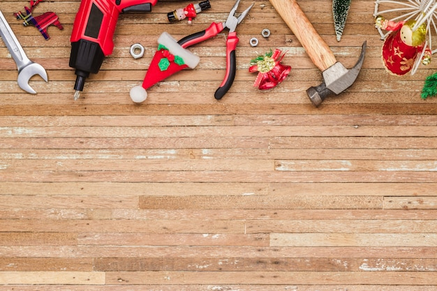 Handy construction tools with christmas ornaments on wood