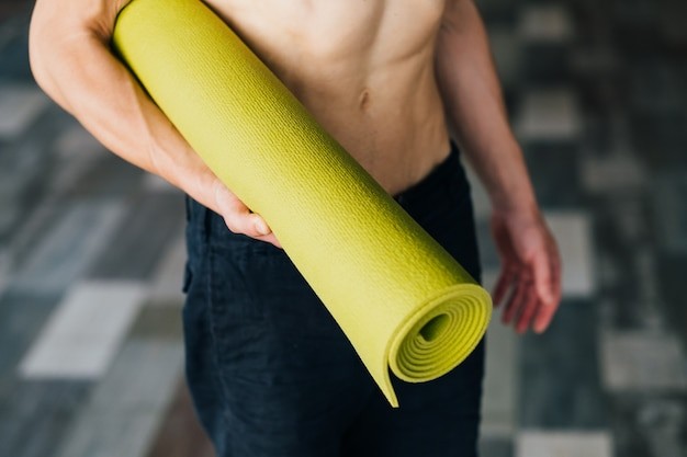 Handy and useful yoga mat for the best training performance. unrecognizable man holding a bright green mat