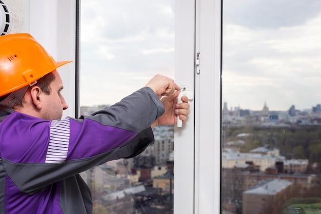 Разнорабочий, регулирующий белое пластиковое окно