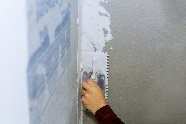 Handyman applying ceramic tiles on bathroom walls in bathroom during renovation