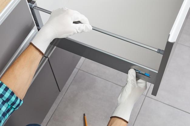 핸디가 조립하고 부엌에 서랍을 설치합니다. 작업자는 가구 메커니즘을 수정합니다.