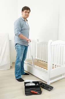 Разнорабочий собирает белую детскую кроватку в новой квартире