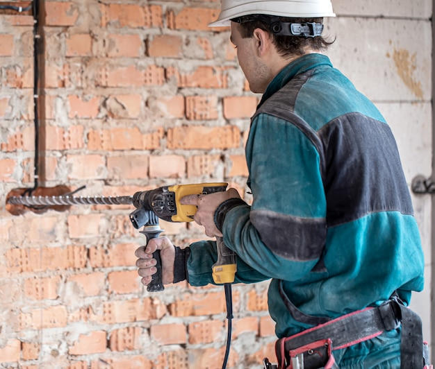 Разнорабочий на стройке в процессе сверления стены перфоратором.