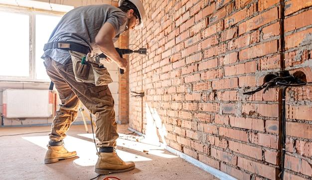 Разнорабочий на строительной площадке в процессе сверления стены перфоратором
