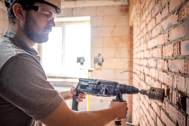 穴あけ器で壁を掘削する過程で建設現場にいる便利屋。