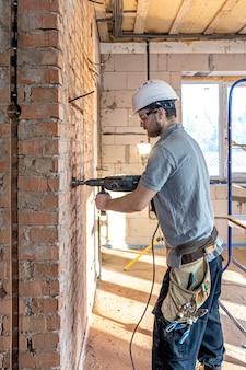 천공기로 벽을 드릴링하는 과정에서 건설 현장에서 잡역부.