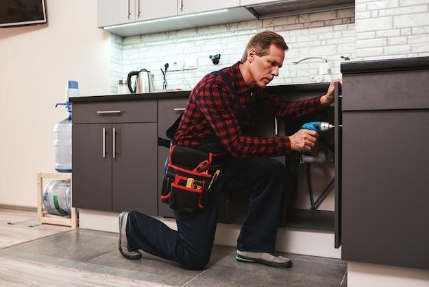 Разнорабочий за работой ремонтирует кухонные полки перфоратором