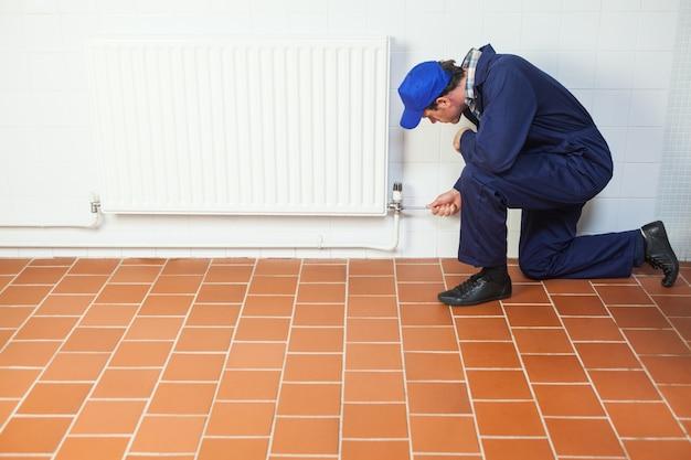 Handyman in blue boiler suit repairing a radiator