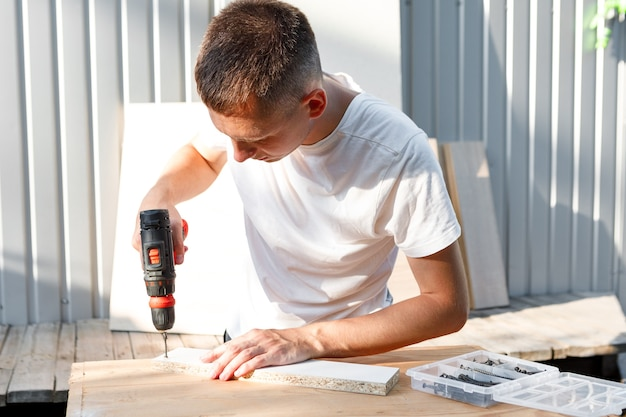 Handyman in blue uniform works with electricity automatic screwdriver house renovation conception