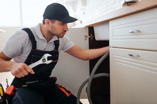 Handyman in cap doing repair