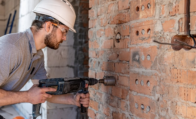 Handyman at a construction site in the process of drilling a wall with an perforator.