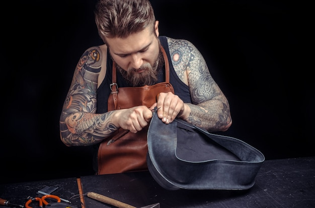 Мастер на все руки создает качественные изделия из кожи в кожевенном ателье. / кожевник за работой на своем рабочем месте.