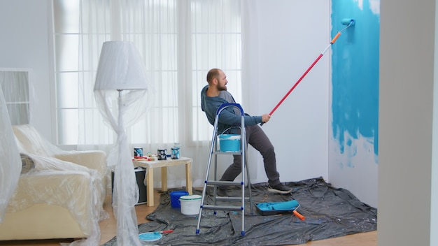 Handyman dancing and painting wall with roller brush while renovating his apartment. apartment redecoration and home construction while renovating and improving. repair and decorating.