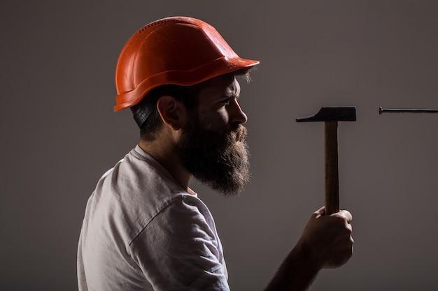 핸디, 망치, 남자 빌더, 산업, 기술, 빌더 개념. 못을 망치로 망치. 핸디 서비스. 하드 모자 빌더, 헬멧. 수염을 가진 수염 난된 남자 노동자, 건물 헬멧, 하드 모자