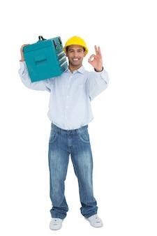 Handyman in hard hat with toolbox gesturing okay sign
