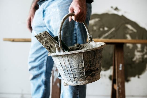 Разнорабочий с корзиной цемента для строительства