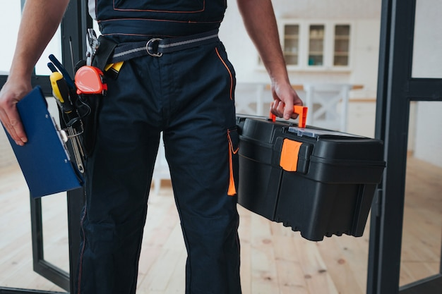 Handyman holding toolbox and plastic tablet in hands