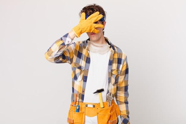 Разнорабочая домработница выглядит шокированной, напуганной или напуганной, закрывая лицо рукой