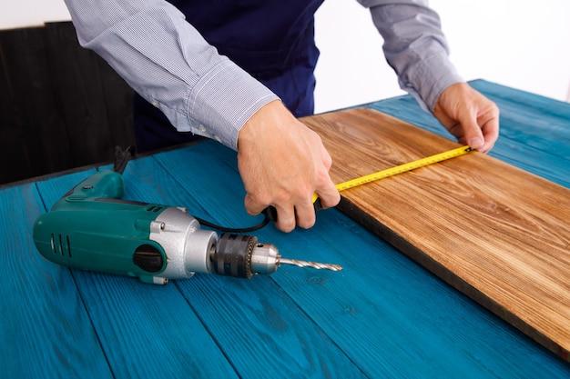 青い制服を着た便利屋は、電動自動ドライバーで動作します。家の改修の構想。