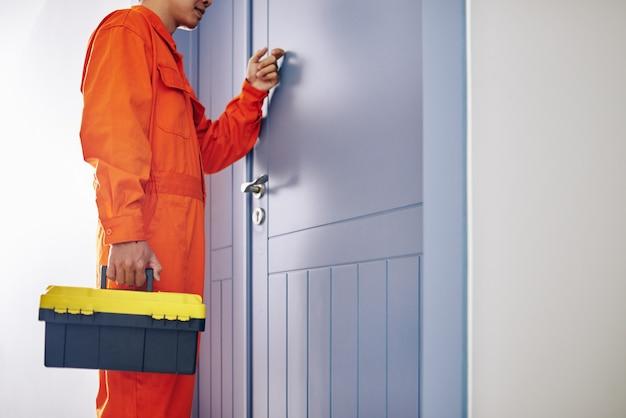 クライアントのドアをノックするツールボックスを保持している明るいオレンジ色の制服を着た便利屋