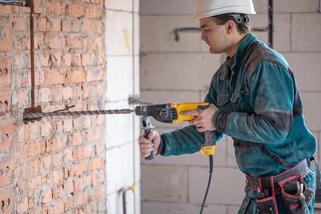 Разнорабочий в процессе сверления стены перфоратором.