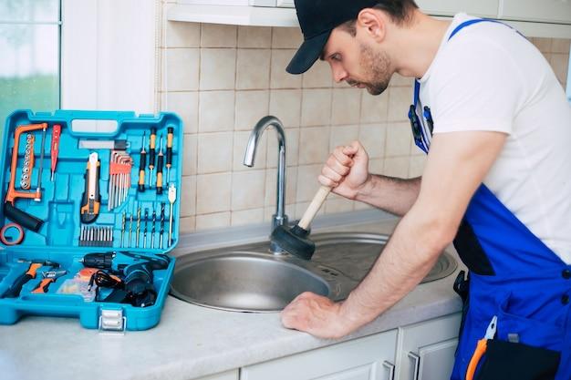 제복을 입은 핸디가 플런저의 도움으로 막힌 주방 싱크를 청소하고 있습니다.