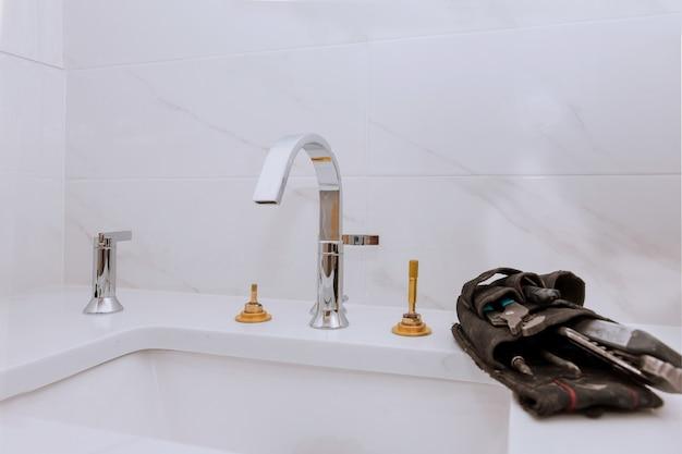 Разнорабочий устанавливает новый смеситель для раковины в ванной комнате