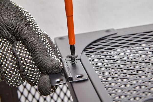 Разнорабочий затягивает винты в дверных петлях плоской мебели с помощью отвертки