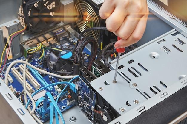 Разнорабочий откручивает винт жесткого диска персонального компьютера, крупным планом.