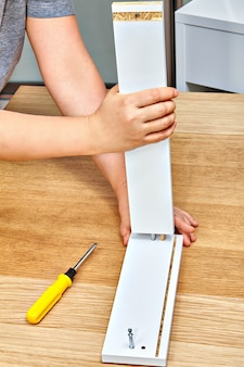 Handyman joins together  two parts of furniture with cam bolt fixings.
