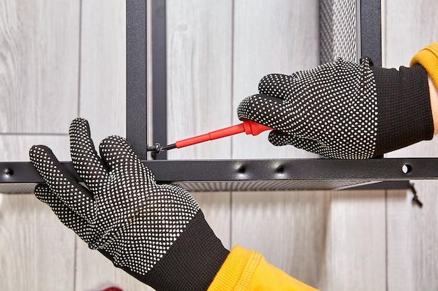 Handyman은 메탈 블랙 프레임으로 플랫 팩 가구 조립을 만듭니다.