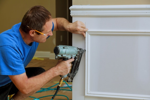 Handyman nailed up picture moulding wall in the new house
