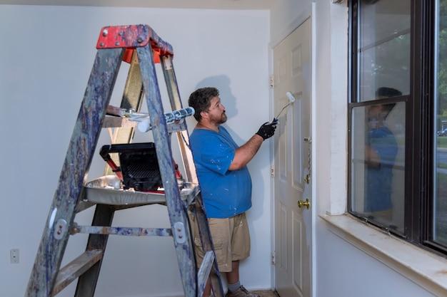 Разнорабочий красит дверной плинтус малярным валиком при ремонте дома