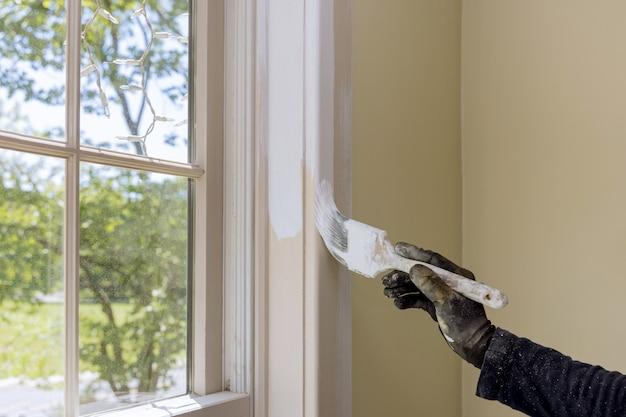 Разнорабочий красит оконную раму при ремонте дома