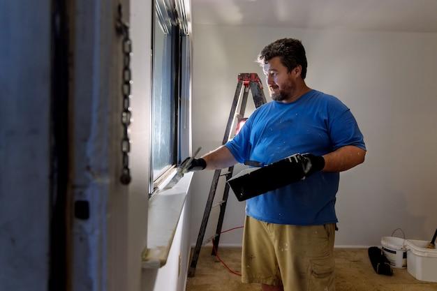 Разнорабочий красит оконный молдинг краской бушат ремонт дома