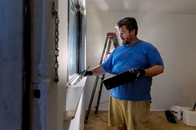 Handyman paints a window molding frame with a paint brushat home renovation