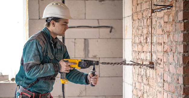 Handyman in the process of drilling a wall with a perforator.